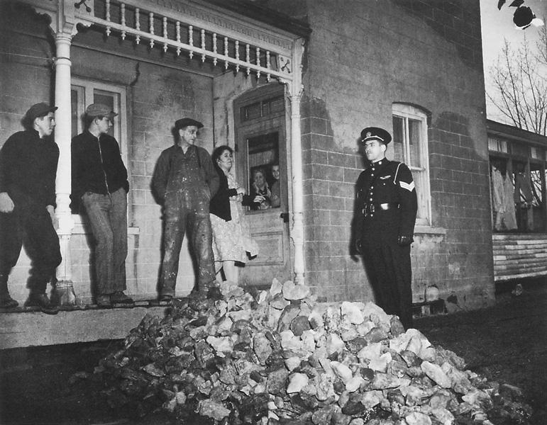 Jack Markow, Près des barrières de l'usine Ayers, à Lachute, un policier garde un tas de roches qu'ont menacé de lancer les grévistes aux briseurs de grève et aux forces de police, le 2 mai 1947. ©Jack Markow/The Gazette (Montréal)/Archives publiques du Canada C53637