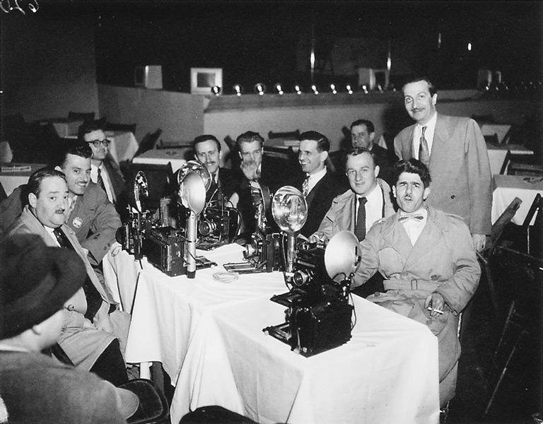 Roméo Gariépy, Des photographes prennent une pause ou Café St-Jacques: Messieurs Robitaille, Deschamps, Pricher, Long, Lowny, O'Neil, Taillefer, debout: Françoys Pilon, le propriétaire du Café, 1951. ©Roméo Gariépy