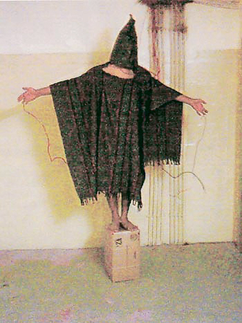 """Photographer Unknown; originally published by The New Yorker, May 10, 2004. An Iraqi prisoner was made to stand on a box for about an hour. He was told that he would be electrocuted if he fell, November 4, 2003. This image may be reproduced only in conjunction with the exhibition """"Inconvenient Evidence: Iraqi Prison Photographs from Abu Ghraib"""" (at the International Center of Photography, 1133 Avenue of the Americas, NY, NY, September 17 - November 28, 2004). @ Tous droits réservés"""