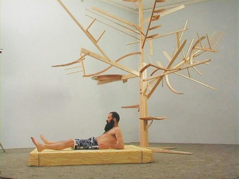 Guy Ben-Ner, Treehouse Kit, 2005, Installation vidéo, Sculpture en bois, tapis et projection vidéo, Dimensions variables. Avec l'aimable permission de Postmasters Gallery, New York, Photo: Richard-Max Tremblay. © Guy Ben-Ner
