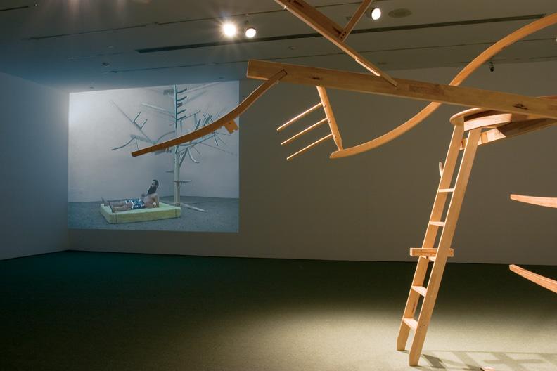 Guy Ben-Ner, Treehouse Kit, 2005, Sculpture en bois, tapis et projection vidéo, Dimensions variables. Avec l'aimable permission de Postmasters Gallery, New York, Photo: Richard-Max Tremblay. © Guy Ben-Ner