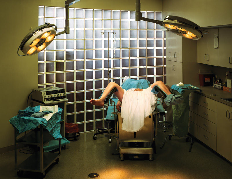 Taryn Simon, Hymenoplasty, Cosmetic Surgery, P.A., Fort Lauderdale, Florida, 2007, de la série / from the series An American Index of the Hidden and Unfamiliar, épreuve chromogénique / c-print, 95 x 113 cm, © Taryn Simon, permission de / courtesy of Gagosian Gallery The patient in this photograph is 21 years old. She is of Palestinian descent and living in the United States. In order to adhere to cultural and familial expectations regarding her virginity and marriage, she underwent hymenoplasty. Without it she feared she would be rejected by her future husband and bring shame upon her family. She flew in secret to Florida where the operation was performed by Dr. Bernard Stern, a plastic surgeon she located on the internet. The purpose of hymenoplasty is to reconstruct a ruptured hymen, the membrane which partially covers the opening of the vagina. It is an outpatient procedure which takes approximately 30 minutes and can be done under local or intravenous anesthesia. Dr. Stern charges $3,500 for hymenoplasty. He also performs labiaplasty and vaginal rejuvenation. Cette patiente est âgée de 21 ans. Elle est d'origine palestinienne et vit aux États-Unis. Pour se conformer aux exigences culturelles et familiales sur la virginité avant le mariage, elle a subi une hyménoplastie, craignant d'être rejetée par son futur mari et de faire honte à sa famille. En secret, elle a pris un vol pour la Floride, où l'opération fut réalisée par le Dr Bernard Stern, un chirurgien plasticien qu'elle a choisi par Internet. Le but de l'hyménoplastie est de reconstruire l'hymen, membrane qui recouvre partiellement l'ouverture du vagin chez la vierge. L'opération dure environ 30 minutes et peut être pratiquée sous anesthésie locale ou intraveineuse. La patiente peut quitter la clinique en fin de journée. Le Dr Stern demande 3500 $ pour une hyménoplastie. Il pratique également la labiaplastie et le rajeunissement vaginal.