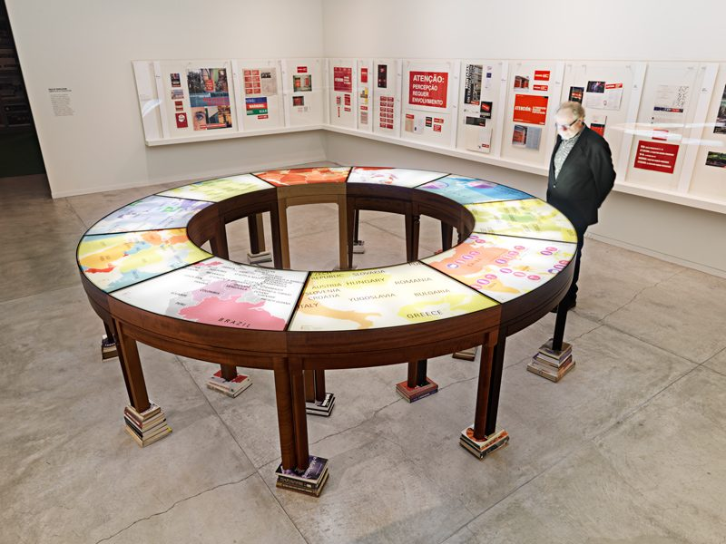 Antoni Muntadas, On Translation: La mesa de negociación II, 2005, wooden table, silkscreened plexiglas, light and books, courtesy of Galeria Joan Prats, photo: Joaquín Cortés / Román Lores, Museo Nacional Centro de Arte Reina Sofía, courtesy of Muntadas / SODRAC