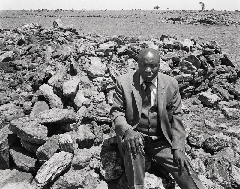 """David Goldblatt, Luke Kgatitsoe in his house, bulldozed in February 1984 by the government after the forced removal of the people of Magopa, a black-owned farm, which had been declared a """"black spot,"""" Ventersdorp district, Transvaal, 21 October 1986,, from the series Structures of Dominion and Democracy, gelatin silver print, 86 x 110 cm, courtesy of the Marian Goodman Gallery"""