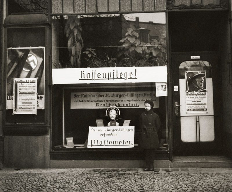 Roman Vishniac, Mara, la fille de Vishniac, posant devant un magasin spécialisé dans la vente d'instruments de mesure du crâne afin de distinguer les «Aryens» des non «Aryens», Berlin, 1933, permission de l'International Center of Photography