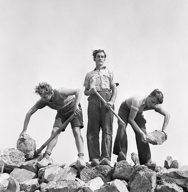 Roman Vishniac, Ernst Kaufmann, au centre, et deux jeunes sionistes non identifiés, en sabots, se formant aux techniques de construction dans une carrière, Werkdorp Nieuwesluis, Wieringermeer, Pays-Bas, 1939, permission de l'International Center of Photography