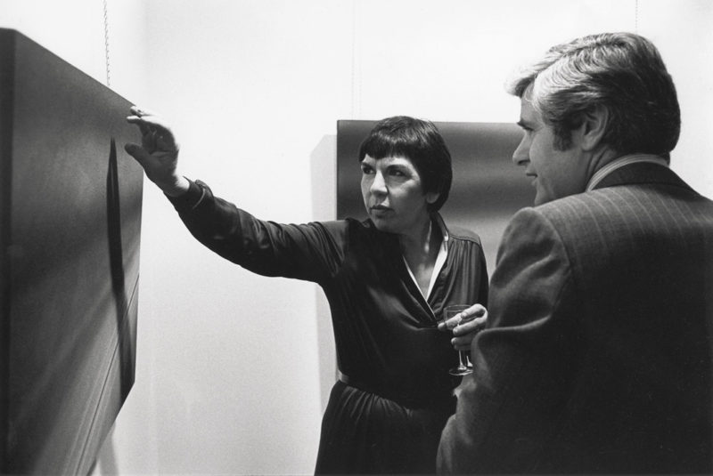 Gabor Szilasi, Rita Letendre explaining a work at the opening of her exhibition at the Galerie Gilles Corbeil, Montreal, November 1980 / Rita Letendre expliquant une œuvre au vernissage de son exposition à la Galerie Gilles Corbeil, Montréal, novembre 1980